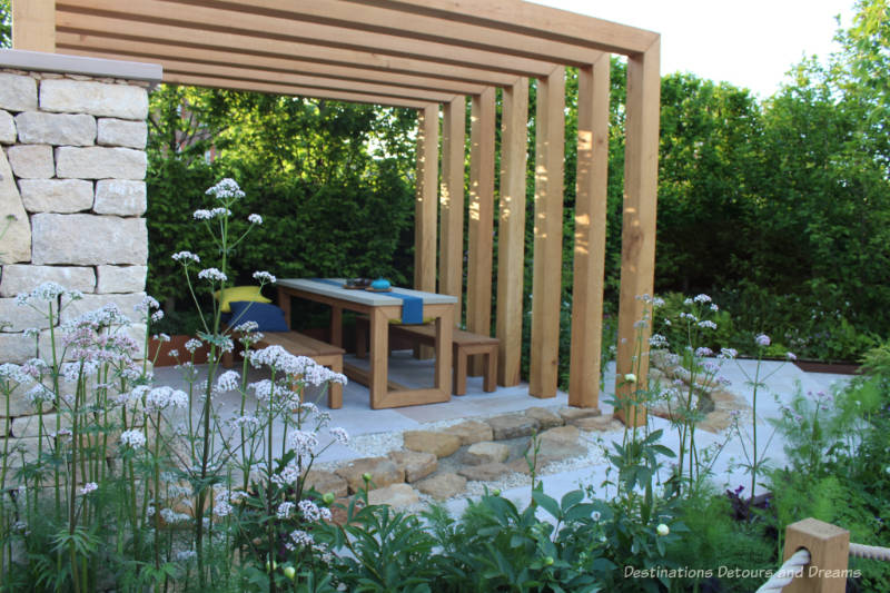 Table and beach in an outdoor seating area covered by a pergola in the Kampo no Niwa Garden at the 2019 Chelsea Flower Show