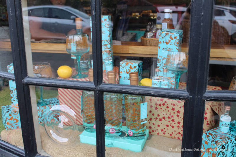 Turquoise and gold bottles and boxes of Silent Pool gin in a store window in England