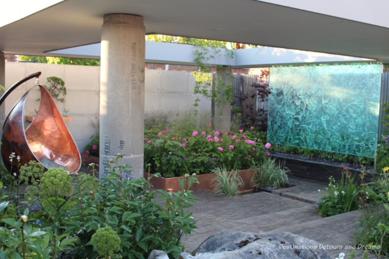 Raised garden bed in area of garden stones with a botanical water wall and bronze hanging chair in the Silten Pool Gin Garden at the Chelsea Flower Show