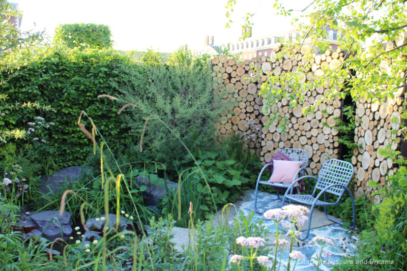 Chairs in a patio area with a wood log wall behind and a pond and wetland plants in front in The Art of Viking Garden at the 2019 Chelsea Flower Show