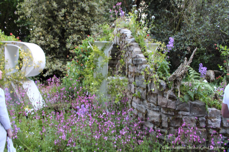 Flowers growing around and up a crumbling stone wall on the Wild Walls display at the 2019 Chelsea Flower Show
