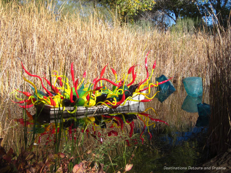 Chihuly sculpture - boat with red and yellow glass pieces and blue crystals in water beside it