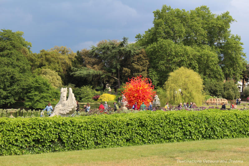 Chihuly's Summer Sun glass sculpture amid plantings and trees at Kew Gardens