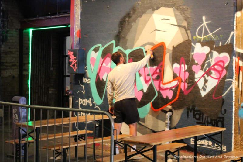 Artist spray painting in London Graffiti Tunnel