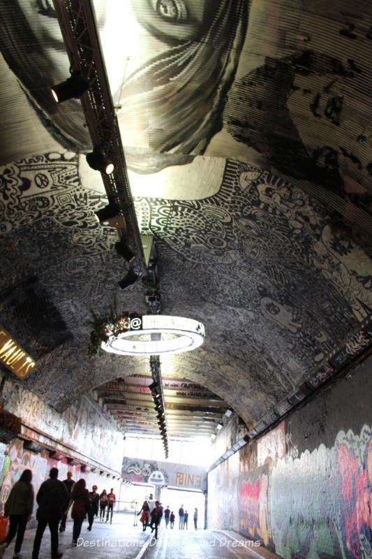 Detailed graffiti art on the ceiling on London Leake Street Tunnel