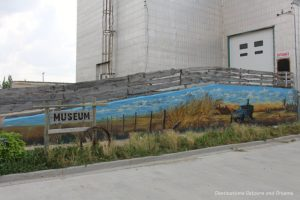 A grain elevator with a mural painted on it houses a museum in Plum Coulee, Manitoba