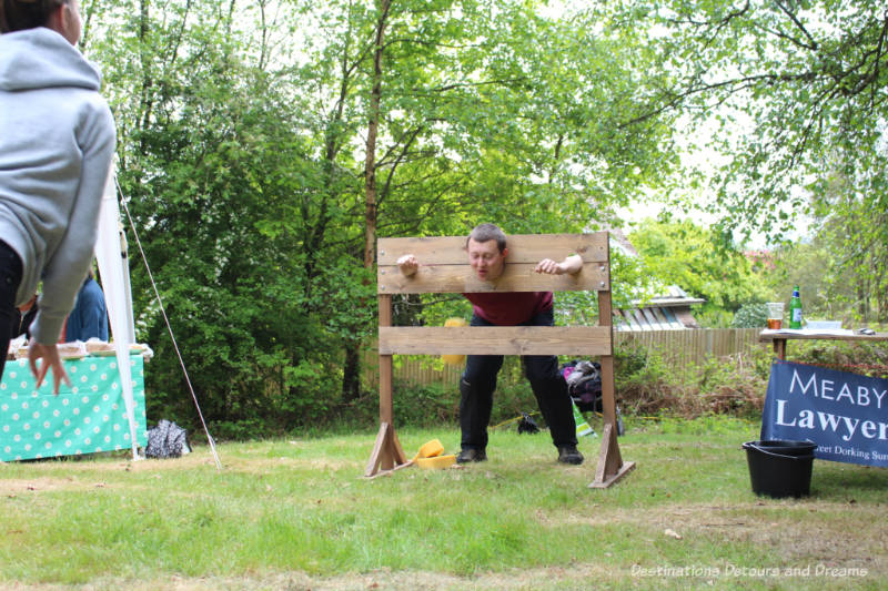 Man in stocks for wet sponge throwing game at an English village fête