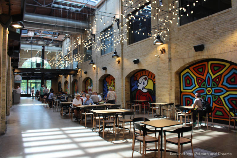 Part of the food court at The Forks Market with aboriginal-style murals on brick walls