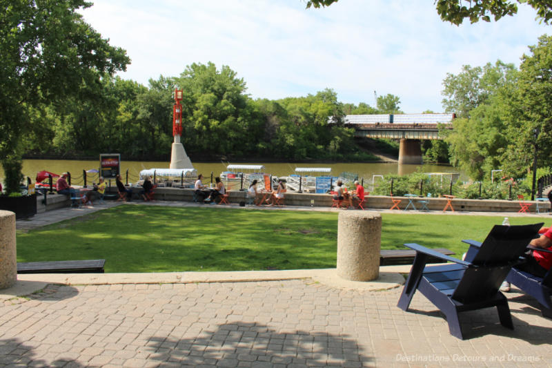 Chairs and bistro tables on The Forks patio overlooking the river