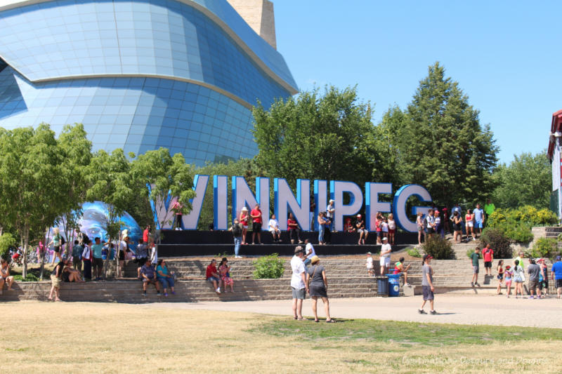 Winnipeg sign with glass panes of the Canadian Museum for Human Rights in the background
