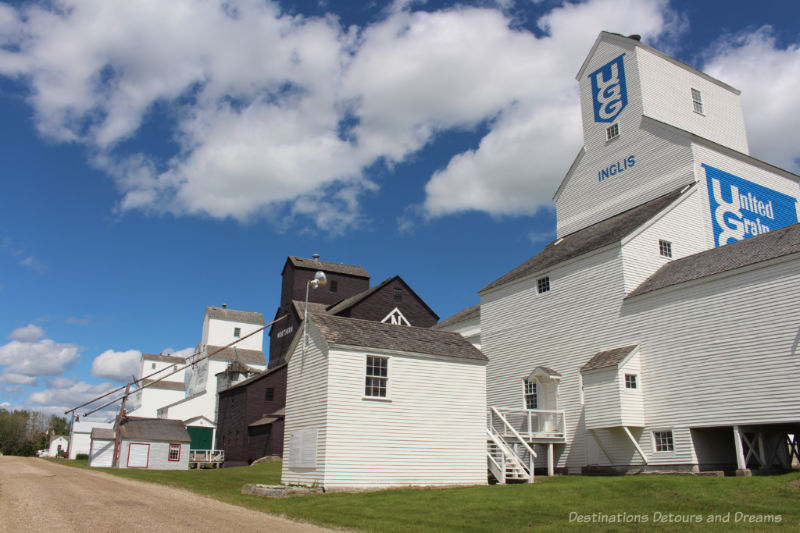 Row of wood grain elevators at Inglis, Manitoba with the UGG elevator in the foreground