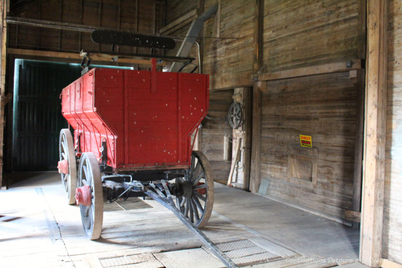 Red grain wagon inside an old wooden grain elevator