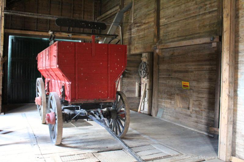 Red grain wagon inside an old wooden grain elevator