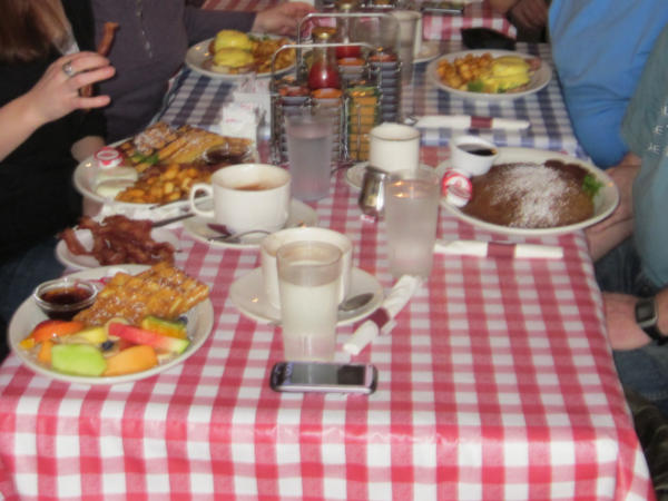 A table with a red and white tablecloth covered with brunch orders at Cafe Zen on Yew in Vancouver