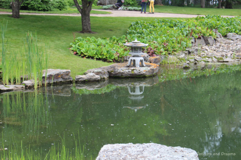 Japanese lantern at the edge of a pond in the Kurimoto Japanese Garden at U of A Botanic Garden