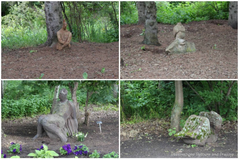 Collection of human-like statues tucked under trees at the University of Alberta Botanic Garden