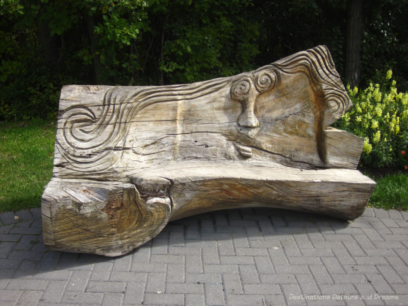 bench carved out of log at a nature playground in Winnipeg, Manitoba