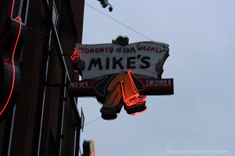 Mikes neon sign features man on a bench reading a Toronto Star Weekly Newspaper at the Edmonton Neon Museum