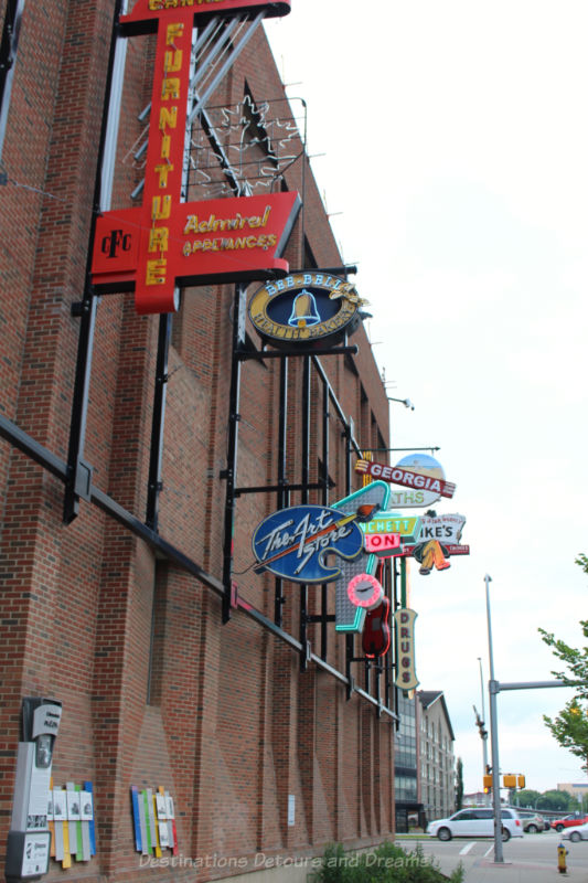 Neon signs along a brick with placards at eye level explaining their history at the Edmonton Neon Museum Signs