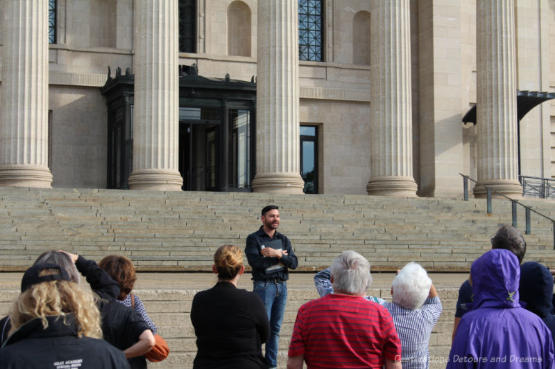 Guide talking to tour group on the steps to the Manitoba Legislative Building
