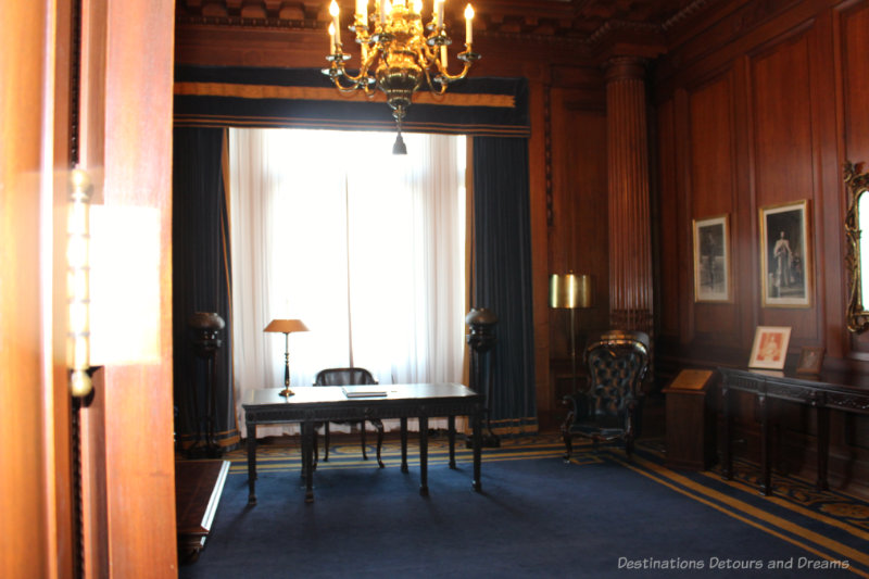 Lieutenant-Governor's Reception Room at the Manitoba Legislative Building has dark wood paneling, blue carpet, and desk as the focal point