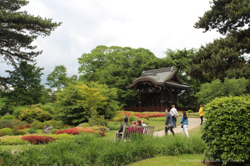 Pathway, bench, shrubs and trees of Japanese landscape at Kew with temple in background