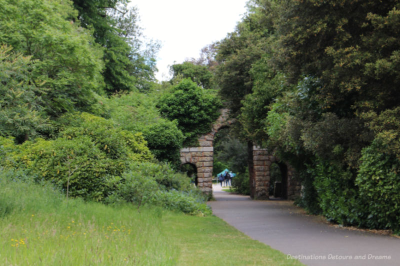 Shrubs and trees growing over a stone wall and doorway at Kew Gardens