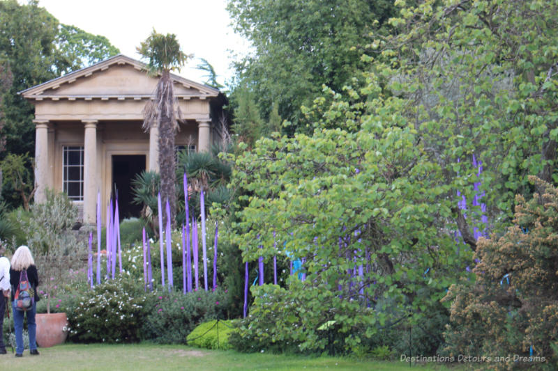 Stone temple amid shrubbery and Chihuly glass art at Kew Gardens