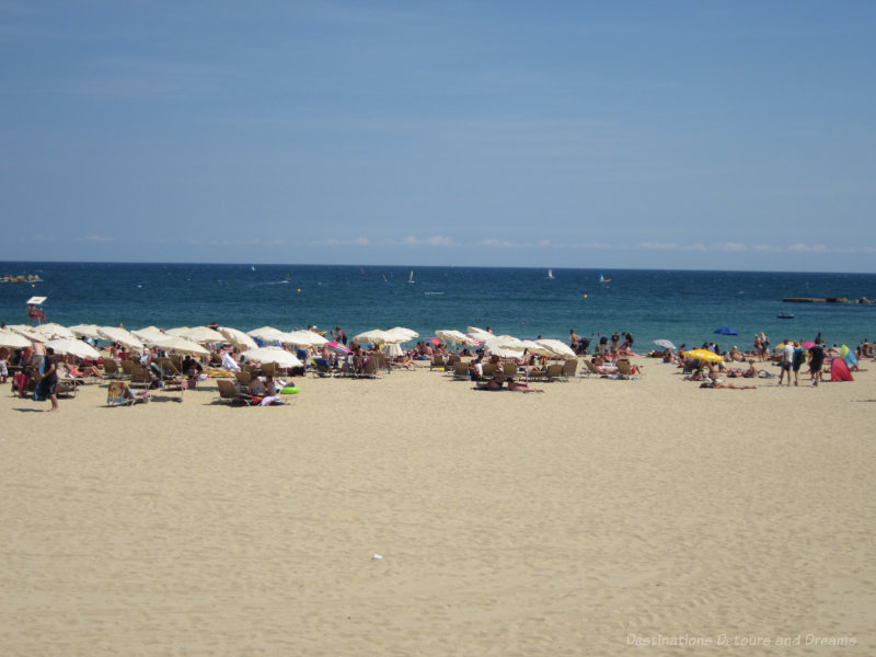 Barcelona beach with people sitting under umbrellas in the sand
