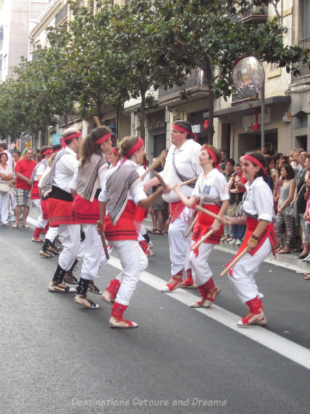 Traditional dancers in white and red with sticks at the Gracia Street Festival parade in Barcelona