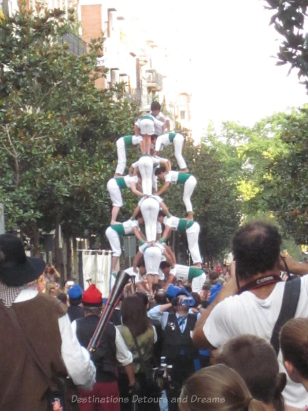 Acrobats forming a human pyramid at the Gracia Street Festival parade