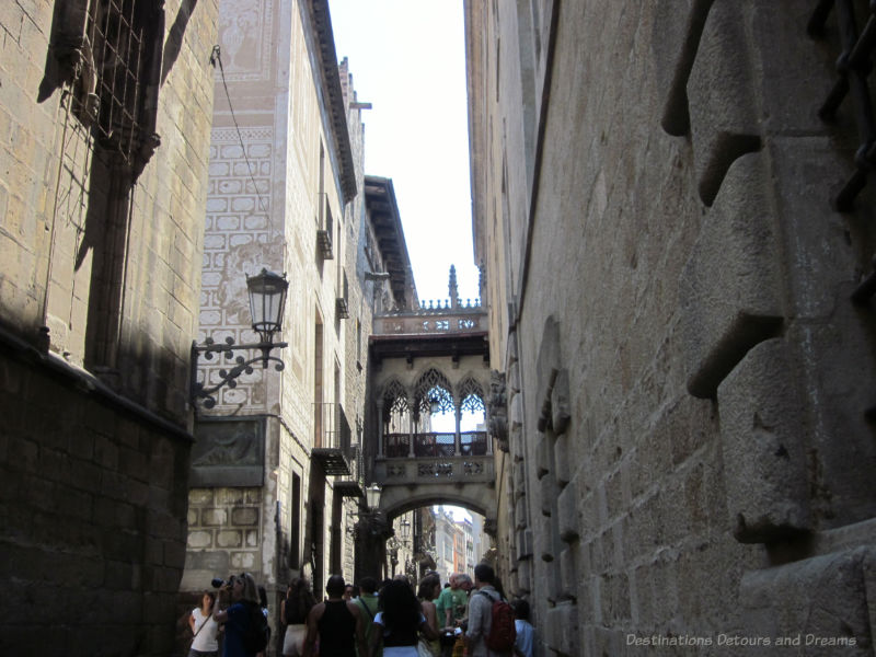 Narrow street lined with old brick buildings and a bridge between them in Barcelona Gothic area