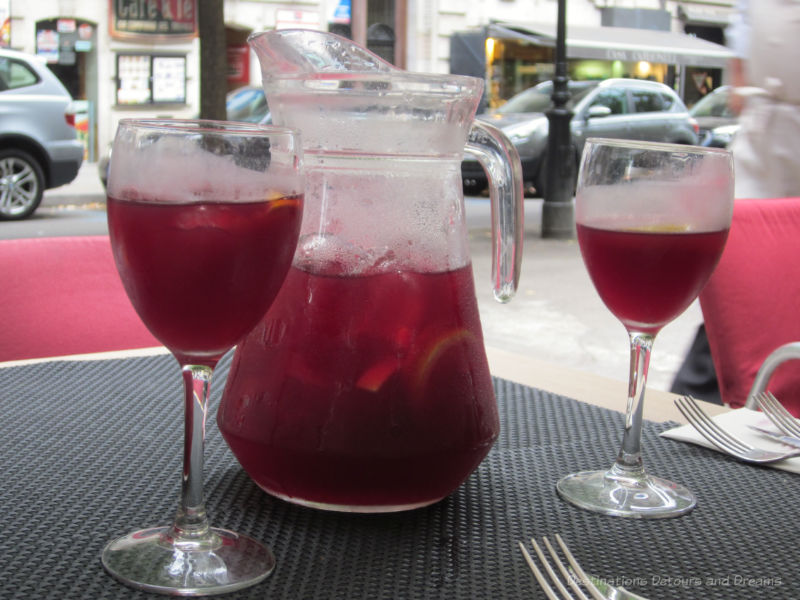 A glass pitcher of sangria with two filled glasses beside it