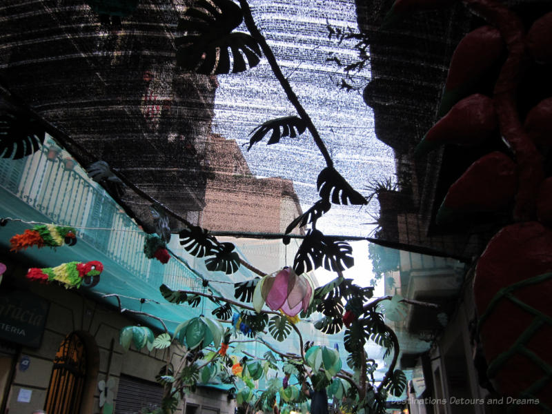 Parrots and other overhead street decorations at the Gracia Street Festival in Barcelona