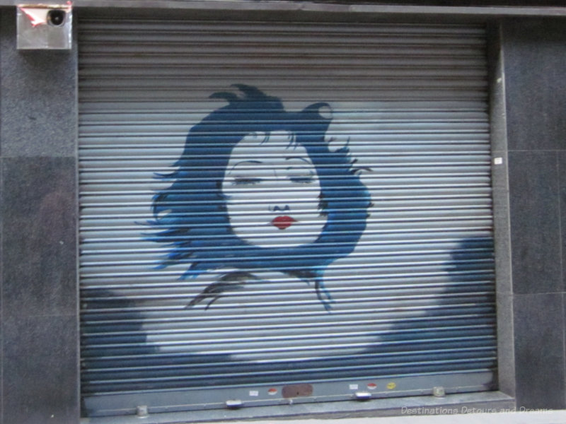 Painting of a woman's face on a metal shop shutter in Barcelona