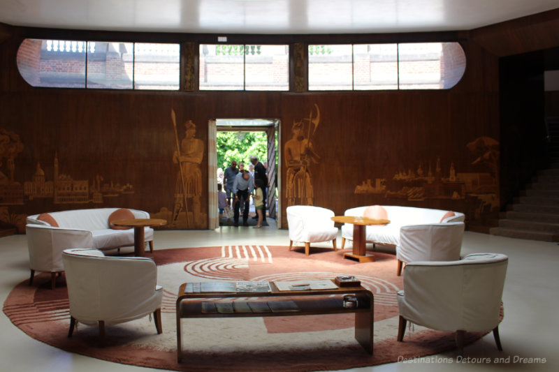 White sofas, reddish-brown circular rug with geometric design, wood wall with marquetry figures and landscapes in Eltham Palace entrance hall