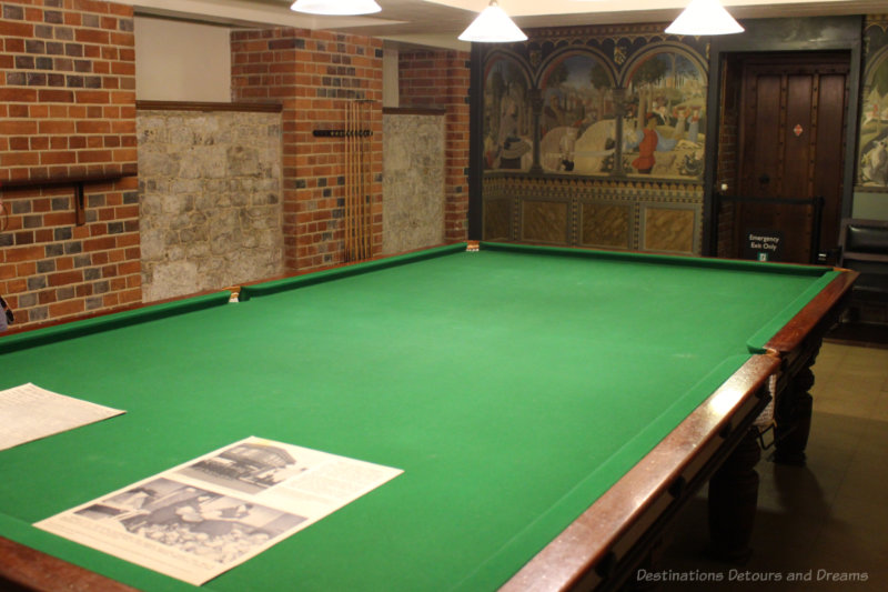 Billiards room featuring billiards table, brick side walls and mural on back wall at Eltham Palace