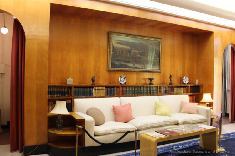 White sofa with wood wall and bookcase behind it at Eltham Palace
