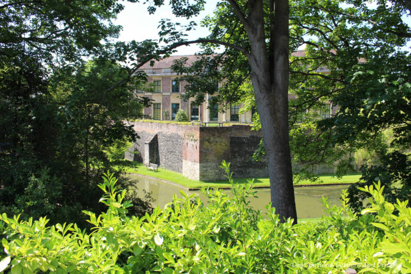 View of brick Eltham Palace through trees and across moat