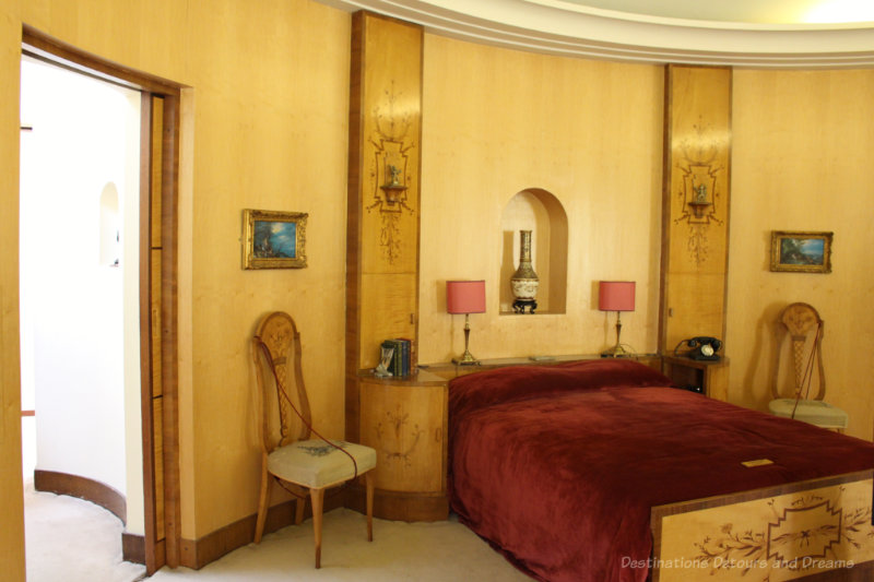 Art deco bedroom with yellow curved wall and decorative wood bedstead and panels beside bed at Eltham Palace