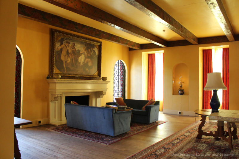 Blue sofas in front of a fireplace in a large room with yellow walls and high, wood-beamed ceilings at Eltham Palace