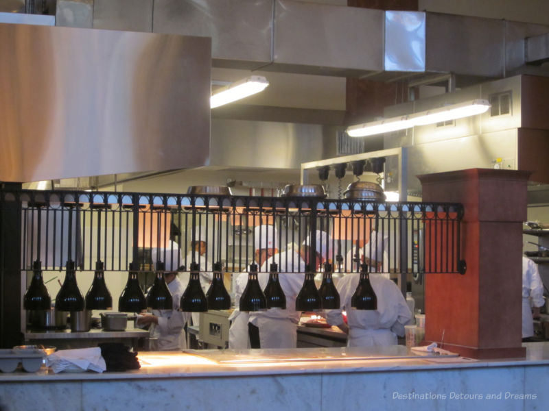 Chefs in restaurant kitchen behind half-wall dividing them from dining area