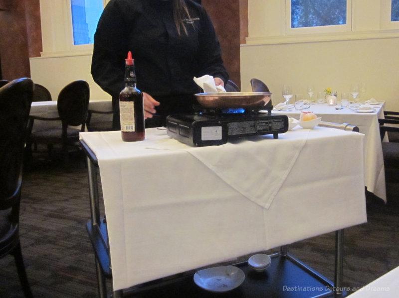 Server preparing flambe dessert at restaurant