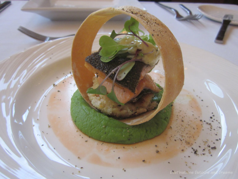 Seared rainbow trout and northern pike cake with horseradish aioli and fresh dill set atop a pea puree, ringed with a crispy potato chip and decorated with carrot paint