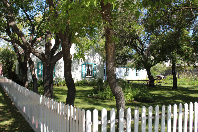 White wooden house with turquoise trim and its white picket-fence trimmed front lawn