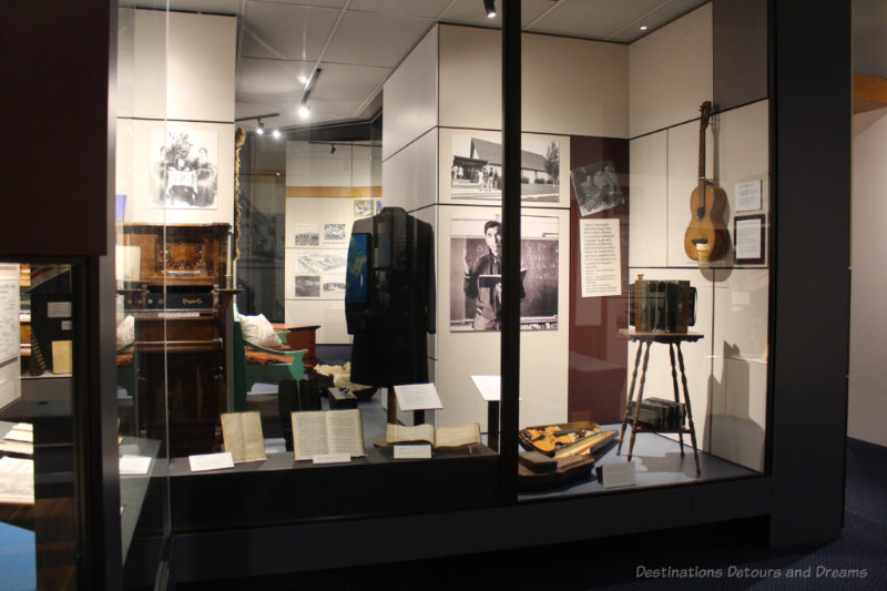 Museum full-size display case with books, musical instruments, photos, and written information