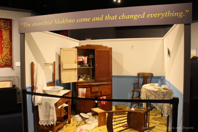 Display of a ransacked house with overturned chair, open cupboards, and broken dishes at the Mennonite Heritage Village