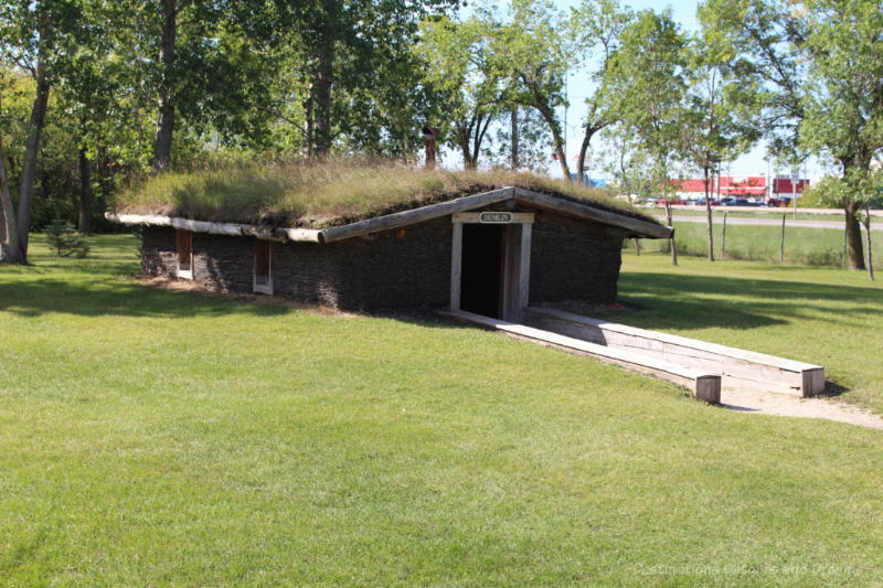 Sod house built partially underground with grass on roof