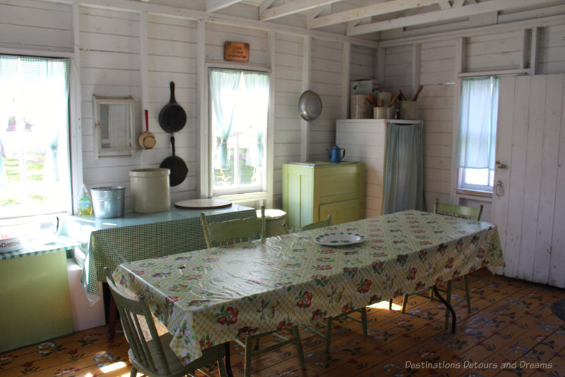 Tables and icebox in a summer kitchen with a wood floor painted with floral designs