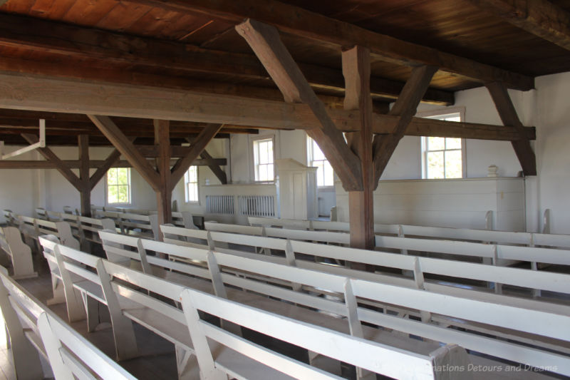 Interior of a plain church building with wood rafters and beams, white walls and white benches